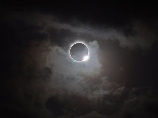 An eclipse partially obscured by clouds (Photo by NASA)