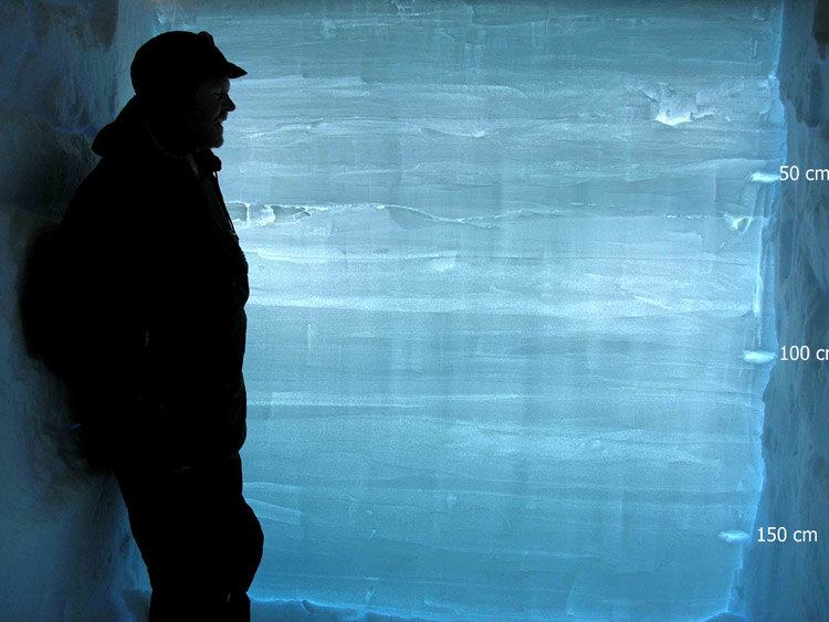Man looking at layers of ice