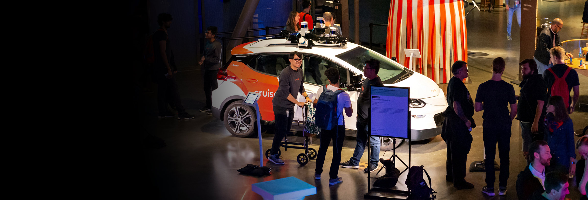 Visitors looking at a Cruise car inside the Exploratorium