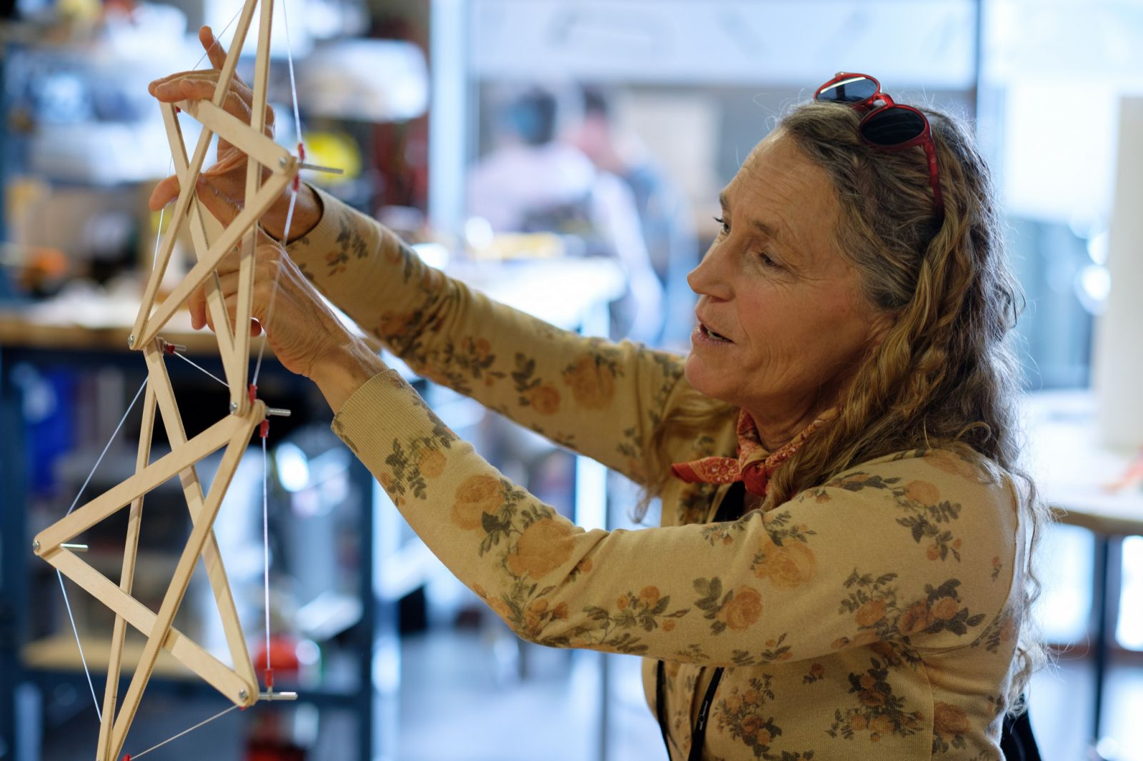 A woman explores a tensegrity model made of craft sticks and rubber bands
