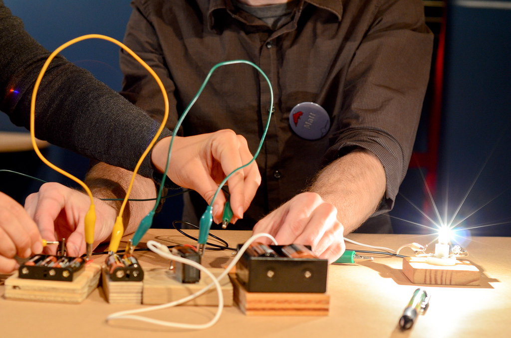 Several adult hands collaborating at making a circuit with wires. A light bulb is brightly illuminated