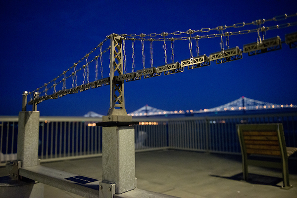 An interactive model of a suspension bridge with a view of the Bay Bridge behind it.