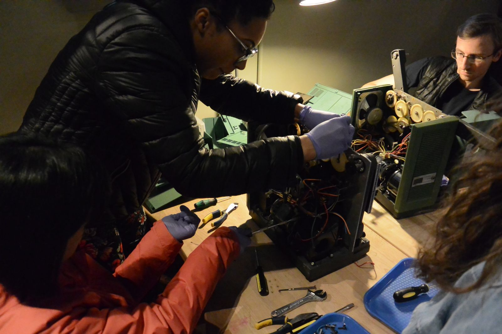 Three adults working collaboratively to take apart two 16mm projectors.
