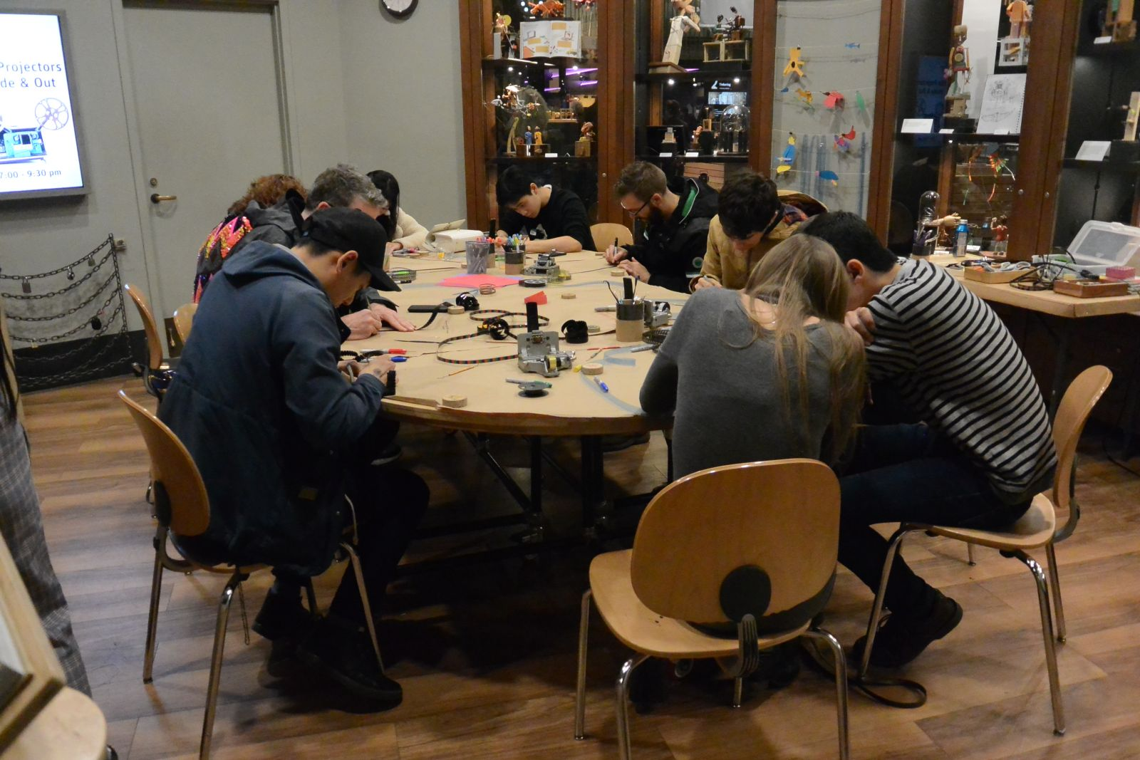 Workshop participants sitting at a wood table making direct animation films.