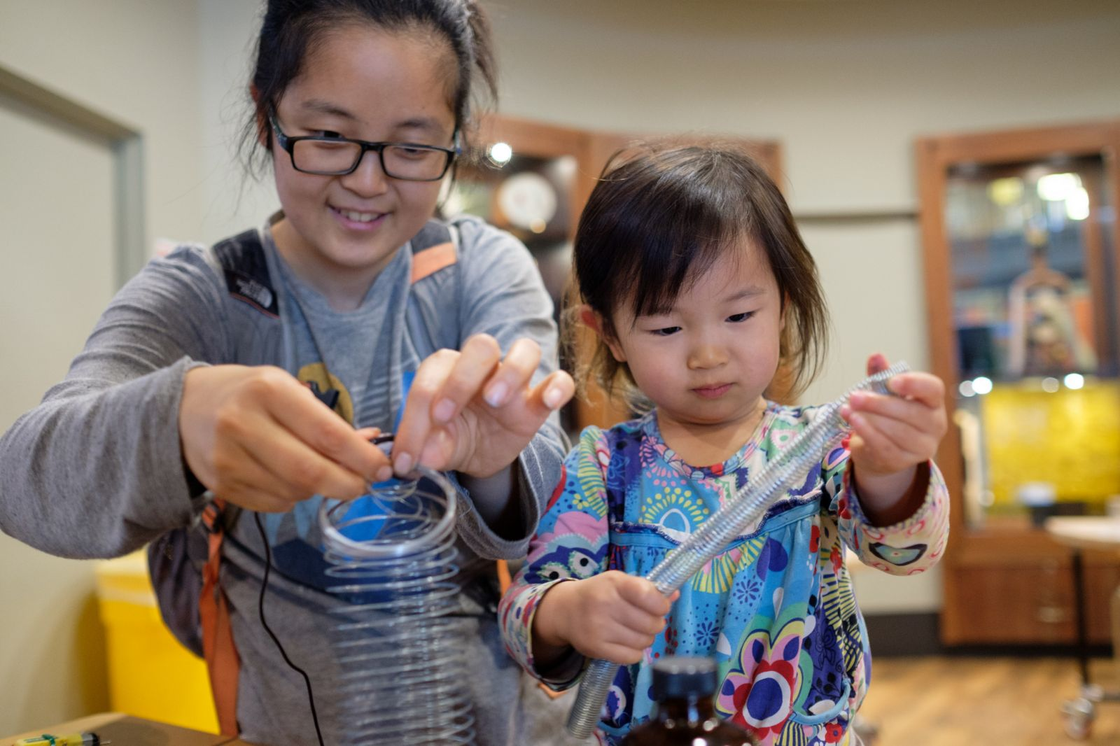 A mother and her daughter exploring metal objects with a piezo microphone