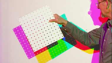 Person holding pegboard making colored shadows