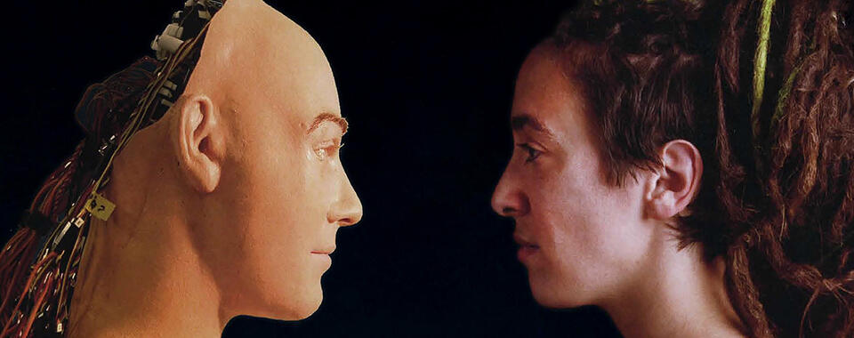 Photo of a person face to face with a mannequin with wires coming out of its head
