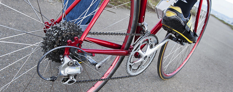 Photo of a red bicycle taken from a low angle, with a foot on one pedal, about to push off.
