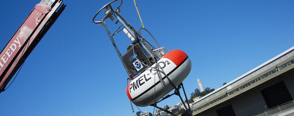 Photo of a big buoy being pulled out of San Francisco Bay with a crane, with blue sky in the background