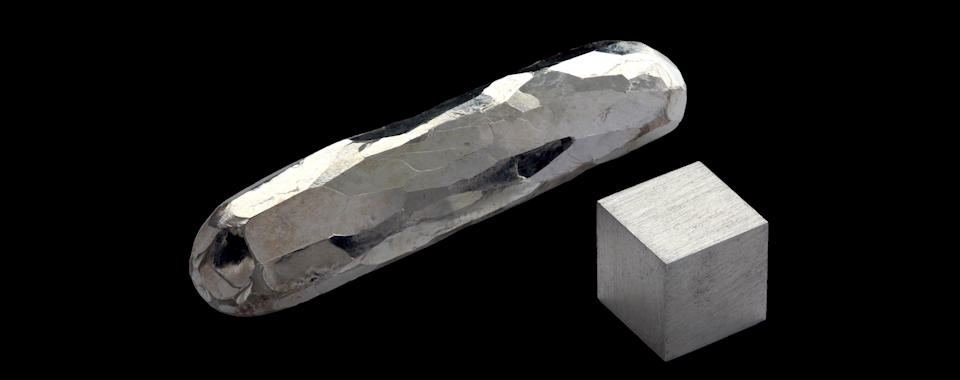 Photograph of a cube and a rough stick of the silvery metal cadmium