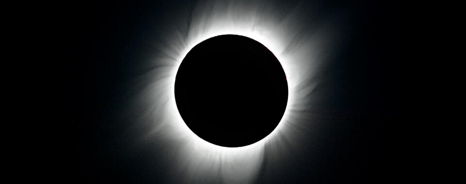 Photo of a black sky and the moon blocking out the sun, showing just the sun's white corona