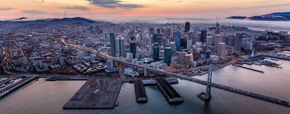 Photograph of San Francisco at twilight, with the fog coming in off the ocean