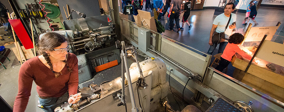Visitors look into the Exploratorium's shop to see exhibit developer Diane Whitmore making custom plastic spacers on a Monarch lathe, a repurposed World War II–era machine obtained in the 1970s from excess U.S. Navy property.