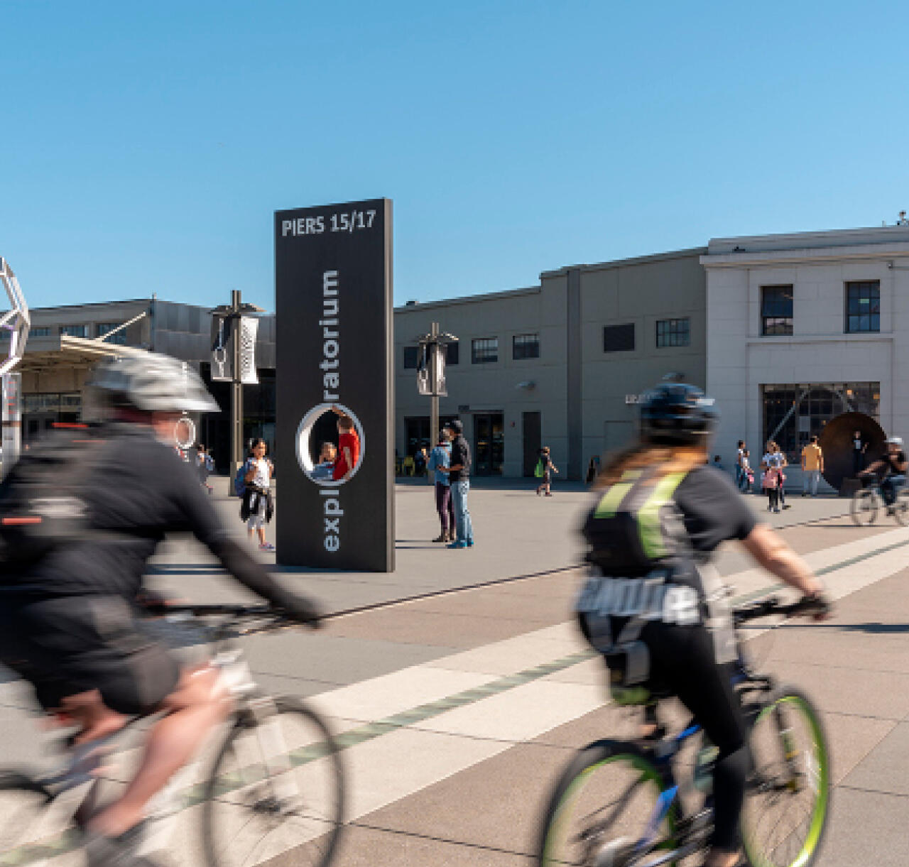 Two bicyclists ride toward the Exploratorium in San Francisco.