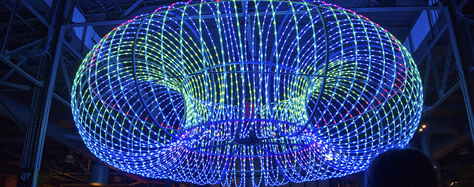 Photograph of a torus of blue and green lights on a dark background