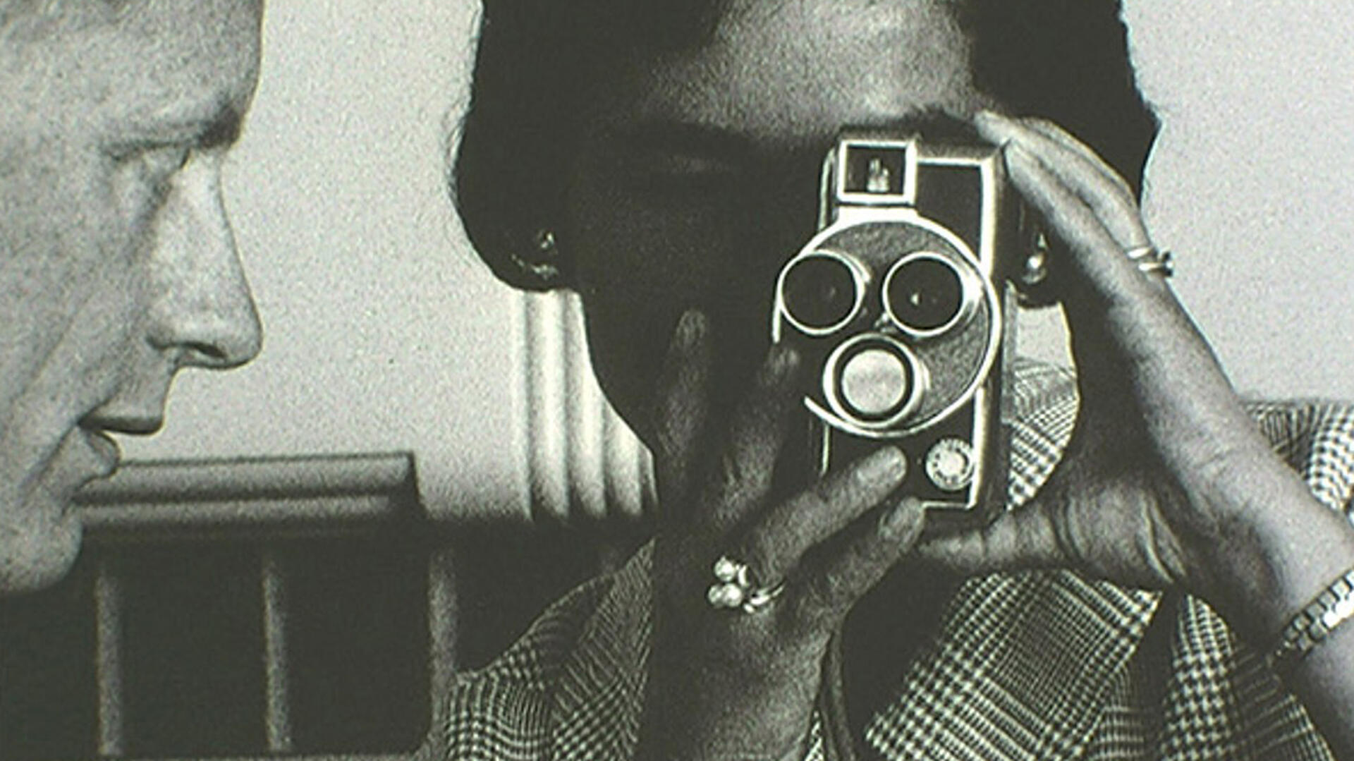 Vintage black-and-white close-up photograph of a woman looking through a film camera