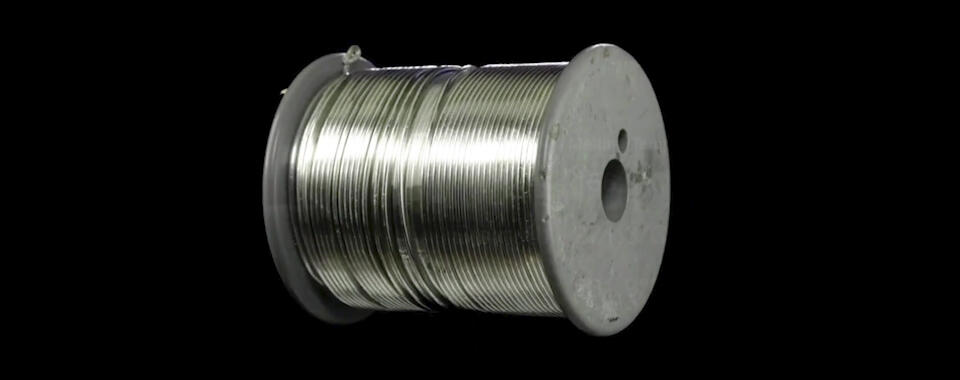 Photograph of a spool of silver-colored wire, presumably indium