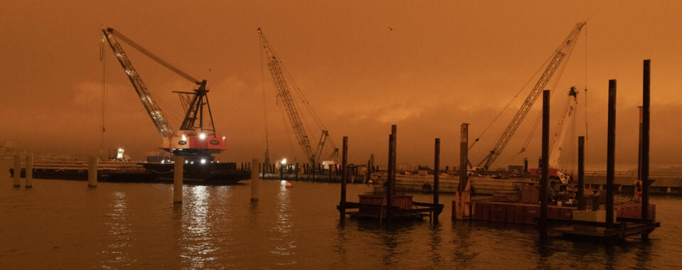 Deep orange skies, polluted by wildfire smoke, reflected over San Francisco Bay