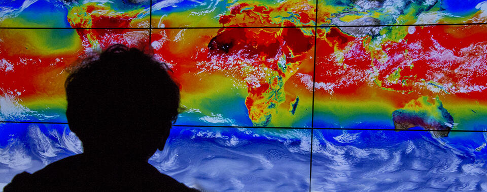 Photo of the silhouette of a person looking at a giant screen showing global temperatures