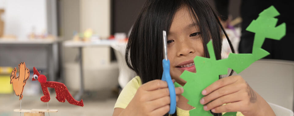 Photo of a little girl cutting a piece of green paper into an elaborate shape with scissors