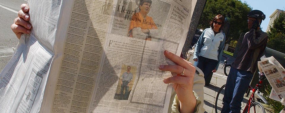 Photograph of a person reading a newspaper