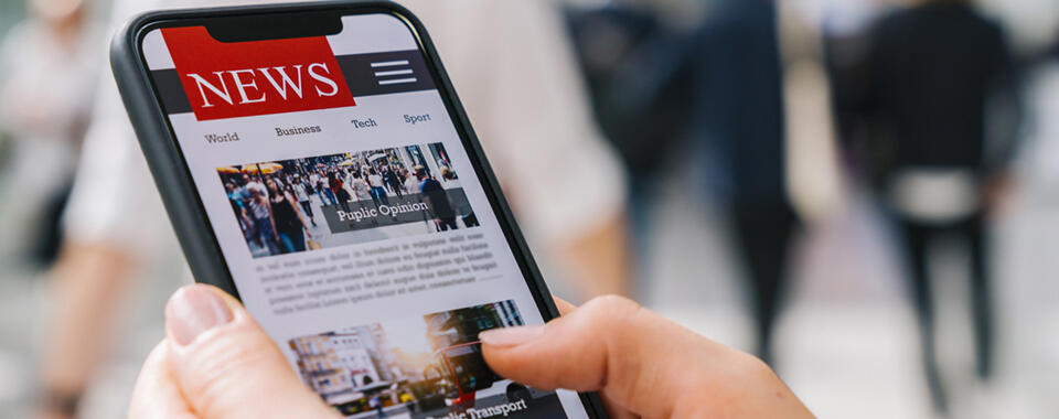 Photo of a pair of hands holding a smartphone displaying a news site