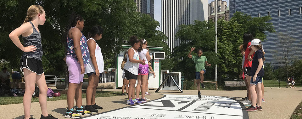Girls interacting with the OUT OF SIGHT hopscotch board.