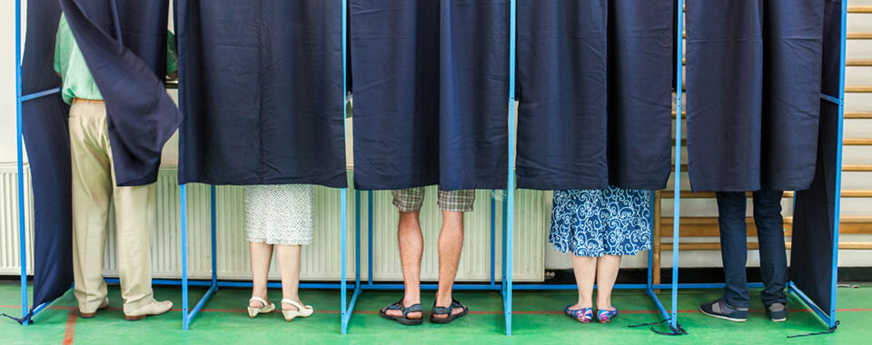 Photo of a row of voting booths with the curtains closed and five different people's legs and feet visible below