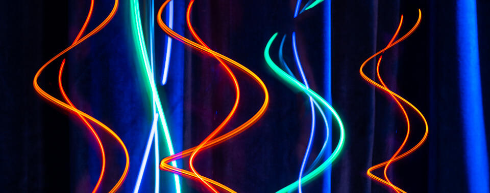 Black background with colored spirals of light flowing down