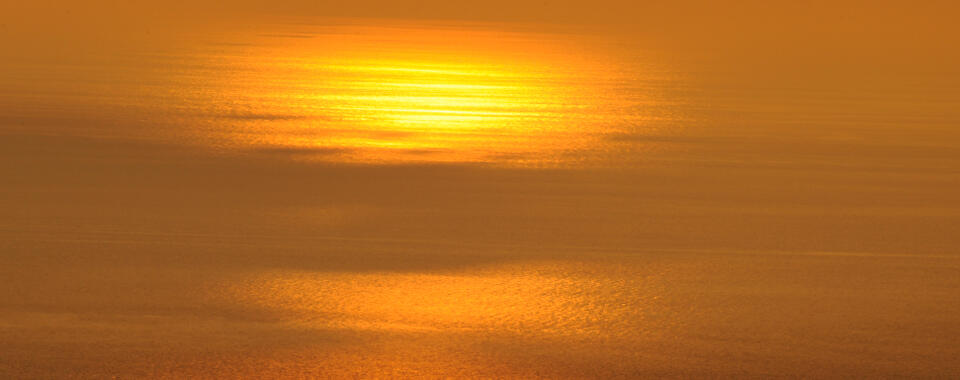 Photo of the sun shining gold on the ocean