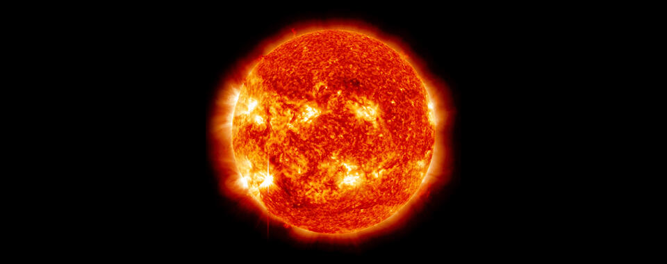 An image of the sun, a big orange ball with bright yellow and white areas, against a black background