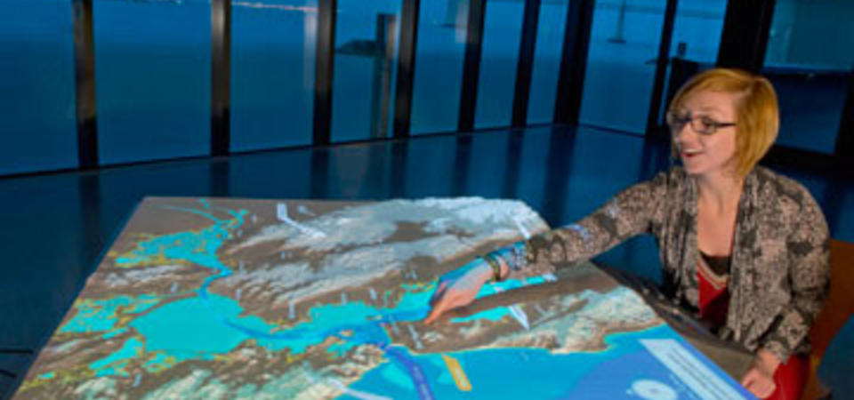 A topographic map of the Bay Area on which data visualizations created by by USGS, UC Berkeley, the National Weather Service, and data artist Eric Fischer are projected. Image by Amy Snyder © Exploratorium, All rights reserved