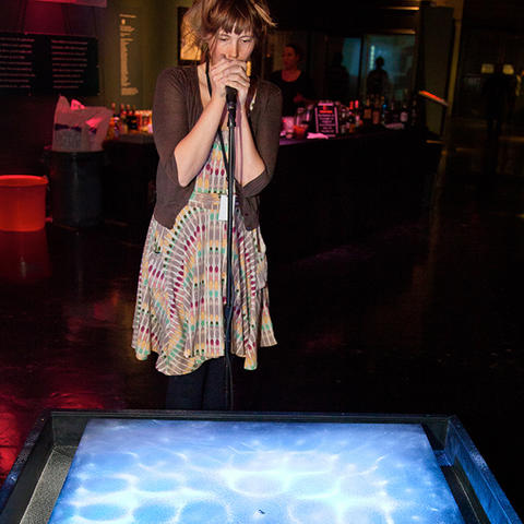 Exhibit developer and artist Meara O'Reilly demonstrates the Chladni Singing exhibit at the Exploratorium