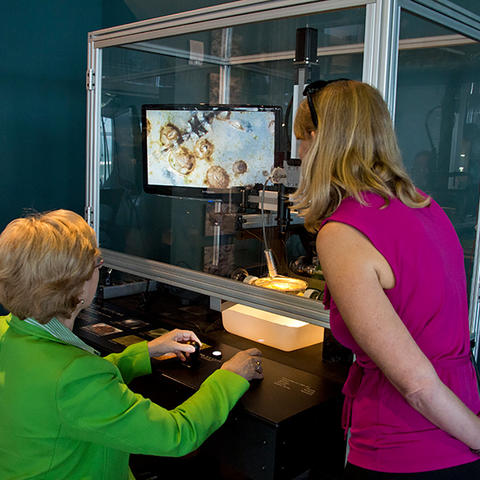 A staff member and visiting guest interact with the Glass Settling Plate exhibit.