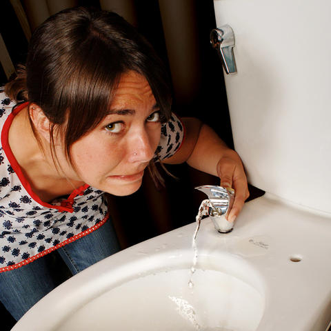 A visitor drinks from a toilet water fountain.