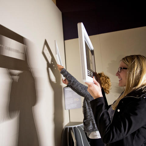 Museum visitors interacting with the Sophisticated Shadows exhibit at the Exploratorium.