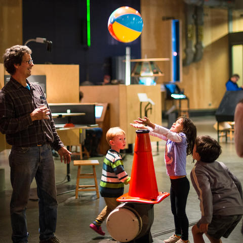 A family plays with the Balancing Ball exhibit.
