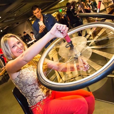 A visitor interacts with the Bicycle Wheel Gyro exhibit.