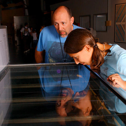 Visitors interact with the Cloud Chamber exhibit.