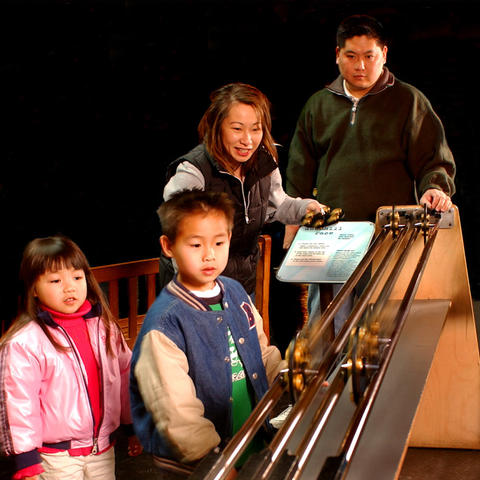 A family plays with the Downhill Race exhibit.