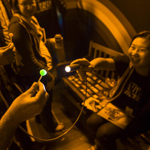 A flashlight reveals the true color of a lollipop inside the Monochromatic Room exhibit.