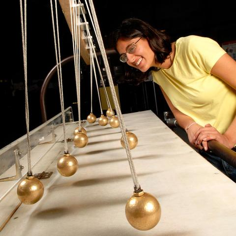 A museum visitor interacts with the Pendulum Snake exhibit