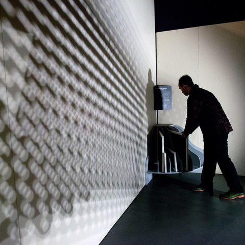 Museum visitor interacting with the Sophisticated Shadows exhibit at the Exploratorium.