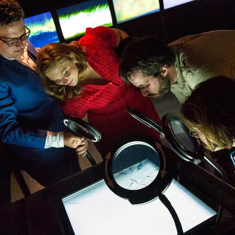 Museum visitors looking at the Watch Water Freeze exhibit at the Exploratorium.