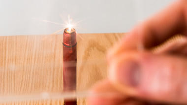 Science activity that demonstrates diffraction using a candle or flashlight bulb and two pencils