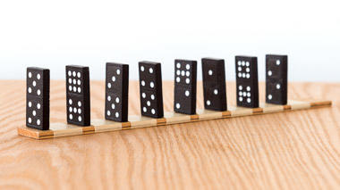 Science activity that uses falling dominoes to model signal transmission in a neuron