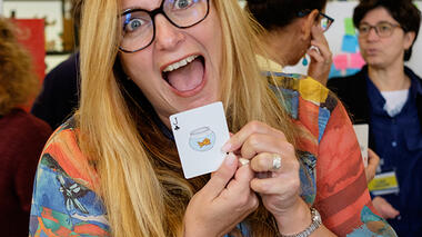 Excited woman holding up a playing card with the drawing of a fish in a bowl on it