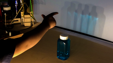 A preschooler points to multiple shadows of a blue bottle
