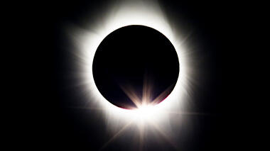 Photo of totality during a total solar eclipse—a black background and the black sphere of the moon passing in front of the sun, with a ring of light around it.