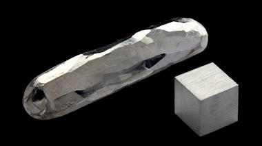 Photo of a small cube and a rough-hewn stick of the silver-colored metal cadmium